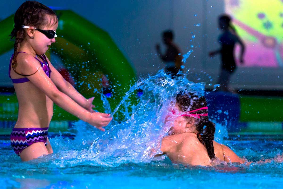 Tyttö läiskyttää vettä toisen päälle Tahko Spassa.
